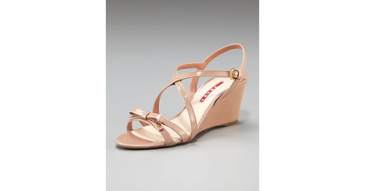 97387bc44232f7 Lyst - Prada Patent Crisscross Bow Wedge Sandal in Natural