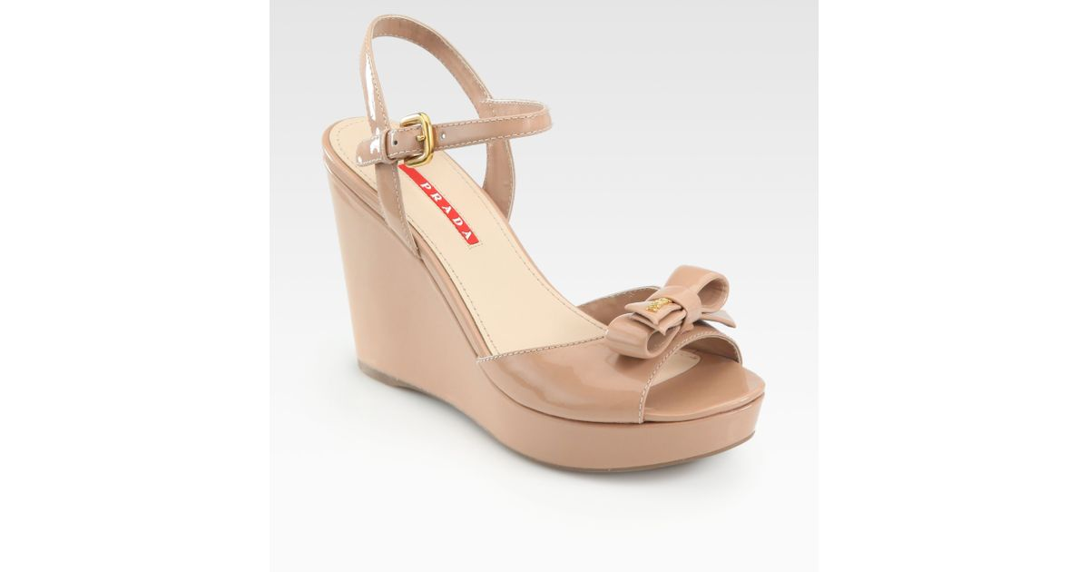 a4025c604c29f Prada Patent Leather Bow Wedge Sandals in Natural - Lyst