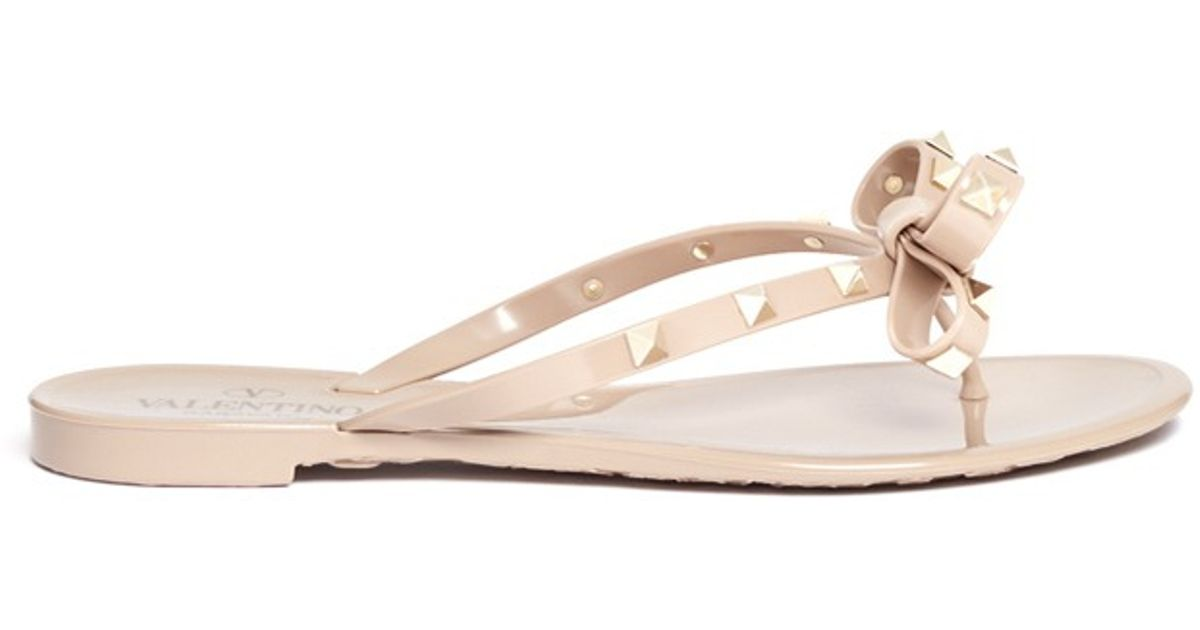 4d1515e0d Valentino Rockstud Bow Flat Jelly Sandals in Natural - Lyst