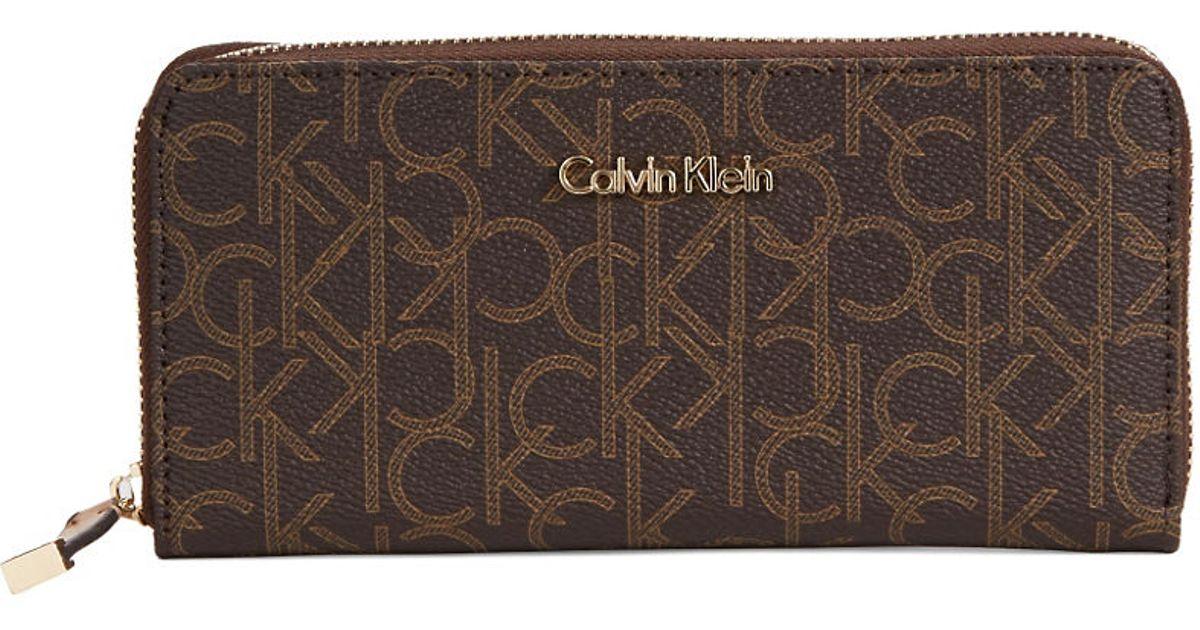 calvin klein monogrammed zip around wallet in brown
