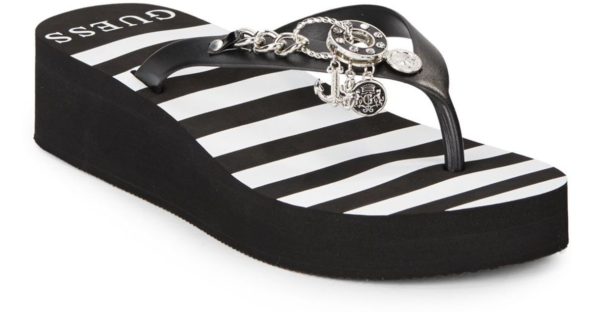 7adf40762b591 Lyst - Guess Striped Charm Wedge Flip Flops in Black