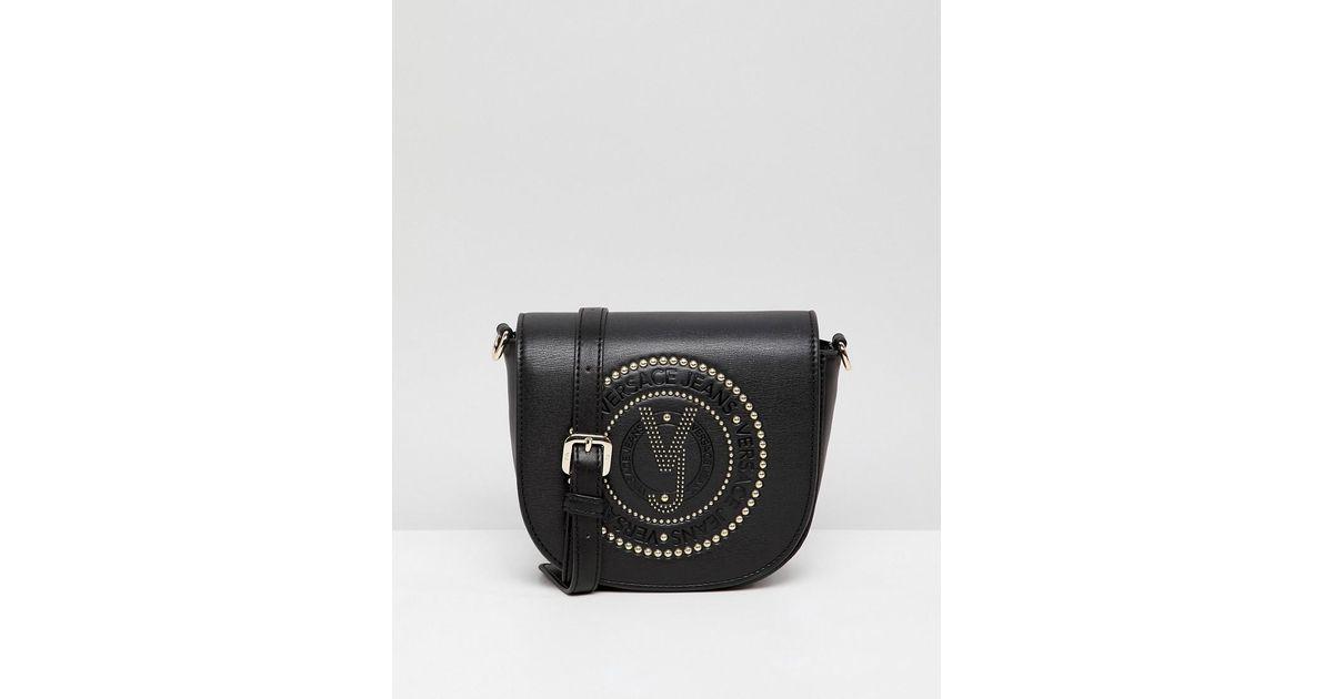 e263f047da Versace Jeans Embossed Logo Saddle Crossbody Bag in Black - Lyst