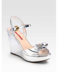 3291b1ec663 Lyst - Prada Patent Leather Bow Wedge Sandals in Metallic