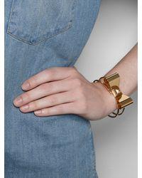 BaubleBar - Metallic Gold Studded Bow Bangle - Lyst