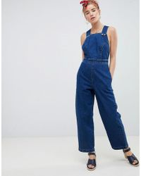 ASOS - Denim Cross Back Jumpsuit In Blue With Popper Detail - Lyst
