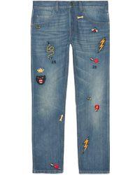 Gucci - Pantalone aderente in denim con simboli - Lyst