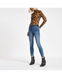 River Island - Mid Blue Mid Rise Ripped Hem Molly jeggings - Lyst