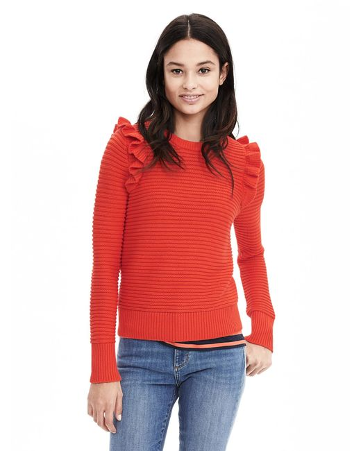 Tomato red sweater featuring a ruffle detailed sleeve. Ultra soft fabric. Relaxed fit.