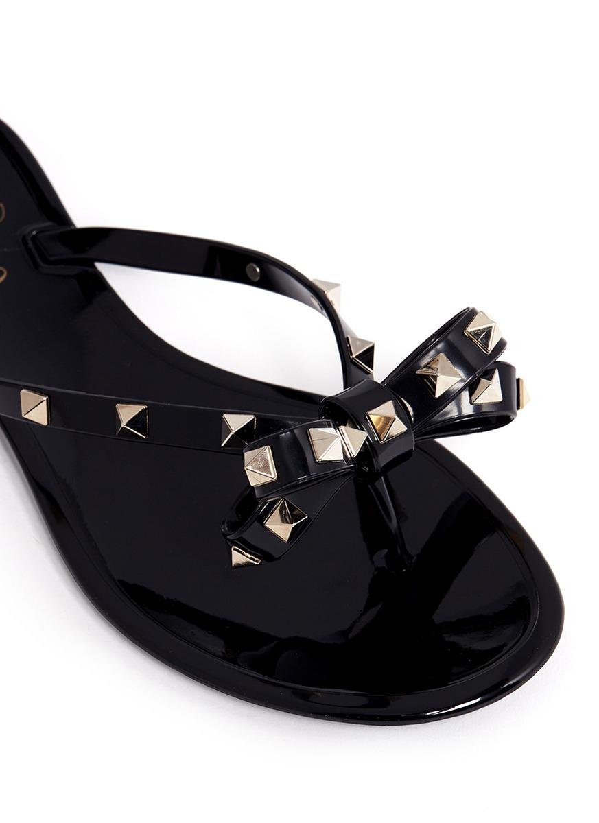3bc5f1fcaaf52c Lyst - Valentino Rockstud Bow Flat Jelly Sandals in Black