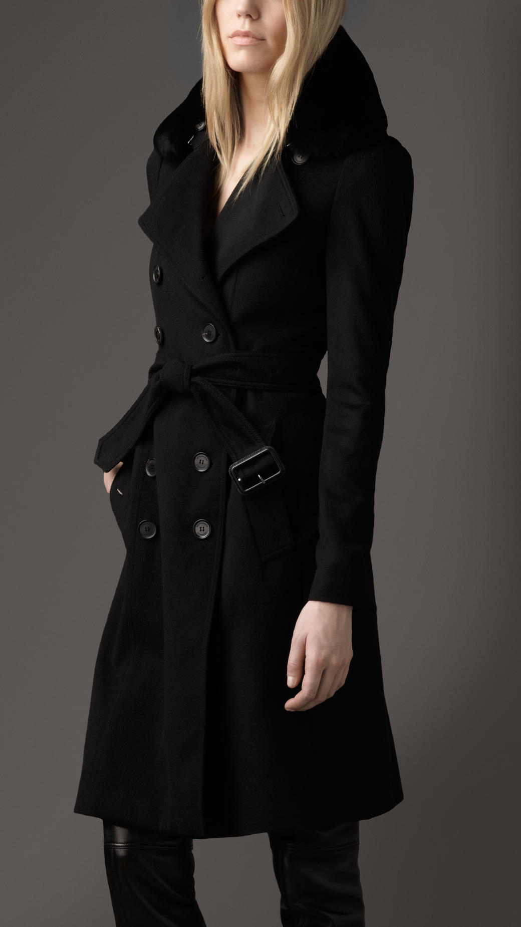 "A women's wool coat with a fox fur collar. This double-breasted black full-length coat has a dyed fox fur shawl collar, long sleeves and a tie belt. The interior is fully lined in black fabric with an ""Anglo Fabrics"" label attached."