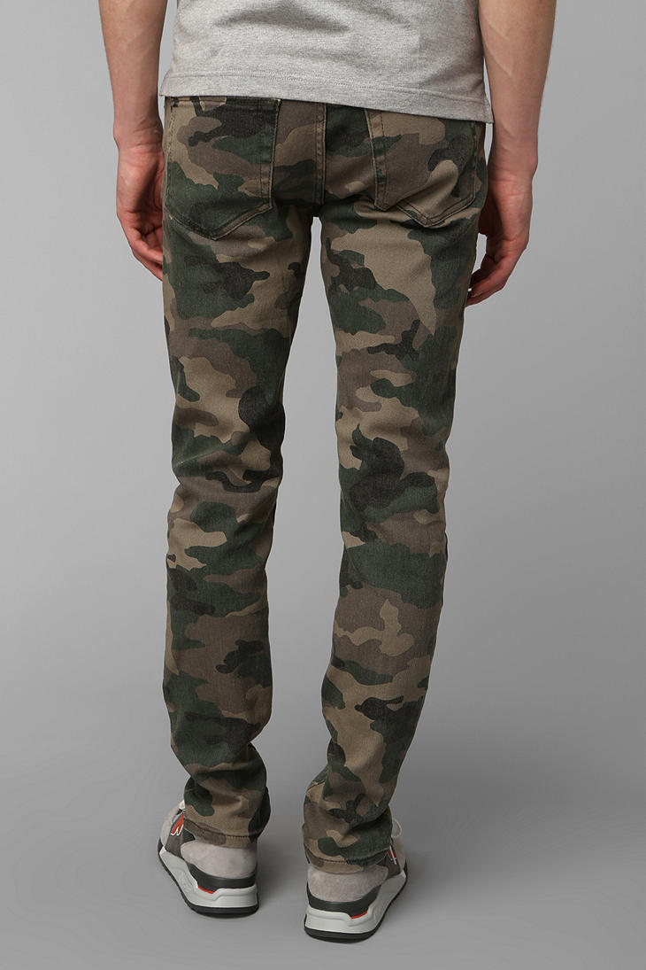 Skinny Camo Pants with Side Stripes. Reach your military goals with these mens skinny camo pants with contrasting side stripes. Camouflage-print pants include five-pocket design, belt loops, and zipper fly.