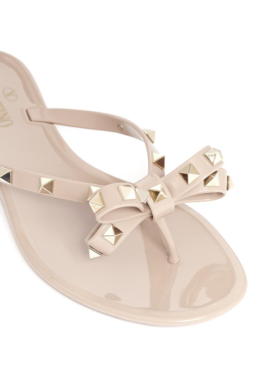 861ebbe05aada3 Lyst - Valentino Rockstud Bow Flat Jelly Sandals in Natural