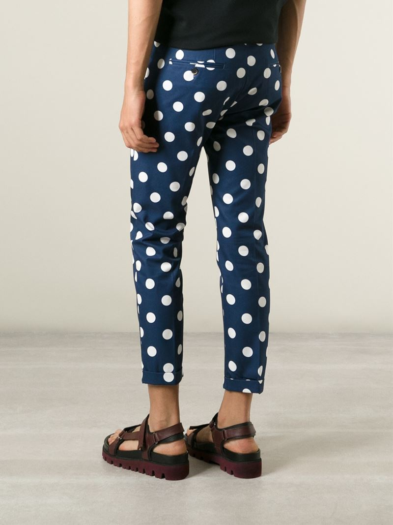 Shop Gucci polka dot trousers at Browns. Blue cotton-wool blend polka dot trousers from Gucci featuring a mid rise, a waistband with belt loops, a front button fastening, side pockets, two back buttoned welt pockets, a bootcut style and a cropped length.