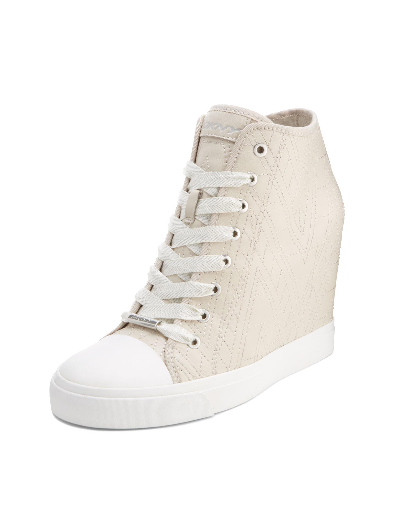 016bb0bb8a88 Lyst - DKNY Grommet Zip Wedge Sneaker in Natural