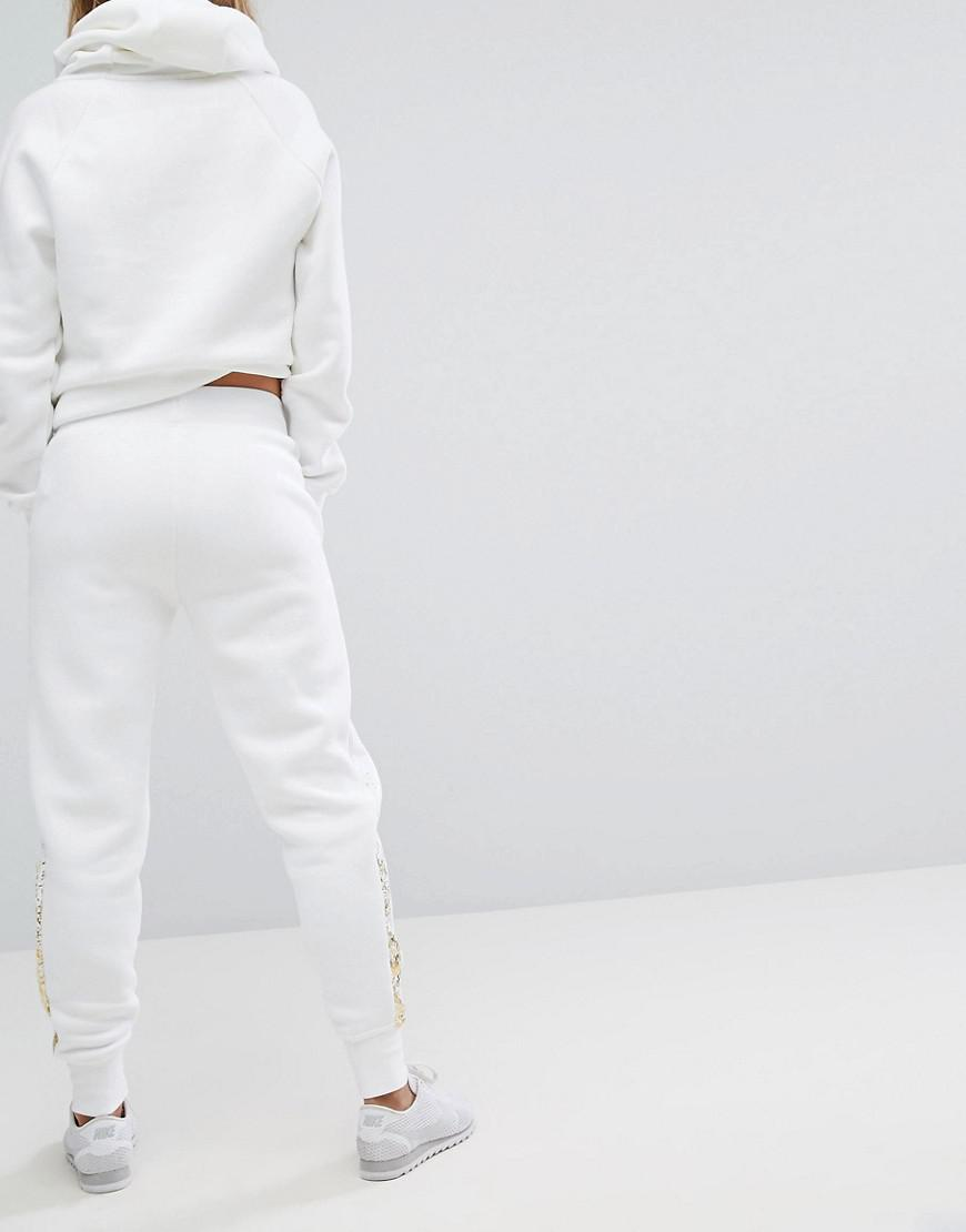 8595fb3e2 Nike Rally Regular Fit Joggers With Metallic Logo in White - Lyst