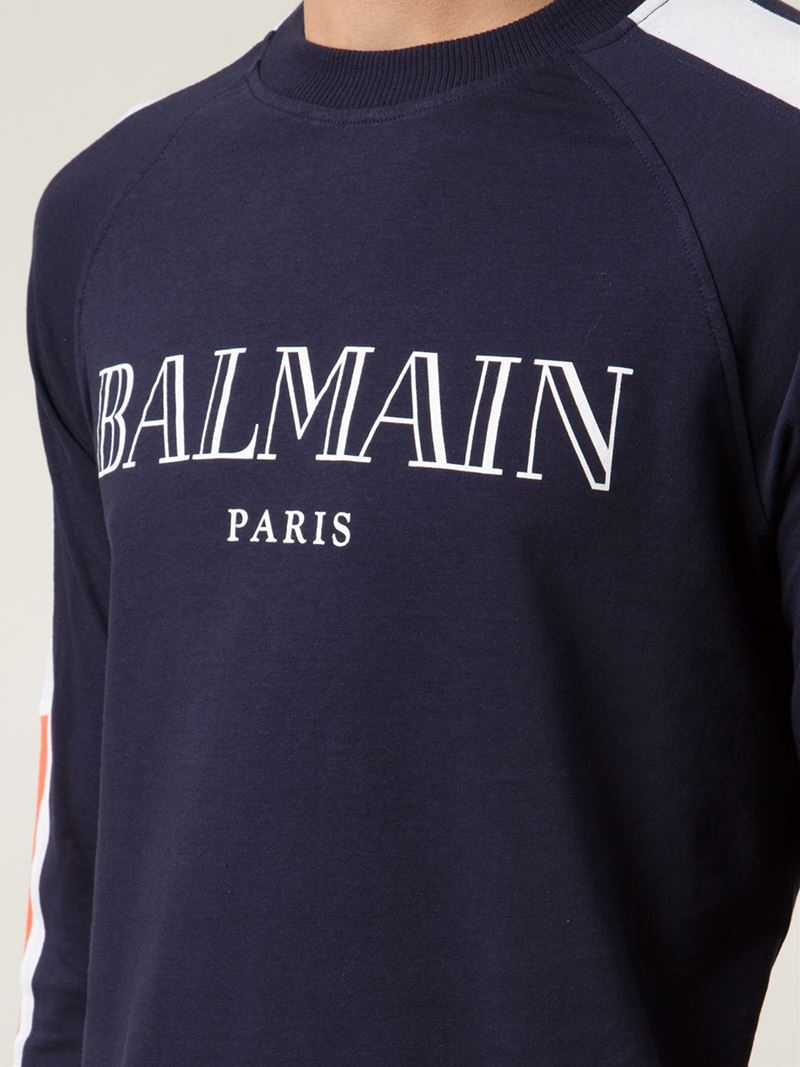 Balmain T-Shirts Refresh your casual portfolio with Balmain T-shirts, from long sleeve Henley tops to classic cotton tees. Heavy on embellishment and regimental detailing, expect logo prints, signature foil detailing and intricate illustrations, perfect for pairing with distressed denim and biker jackets.