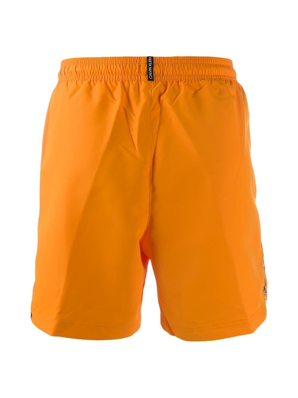 f891b8a2f0c Lyst - Calvin Klein Side Logo Stripe Swim Shorts in Orange for Men